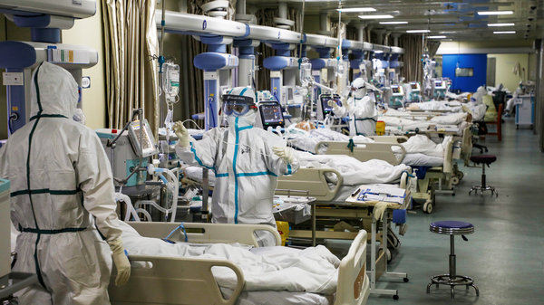 Medical workers in protective suits tend to coronavirus patients at the intensive care unit of a hospital in Wuhan, China.
