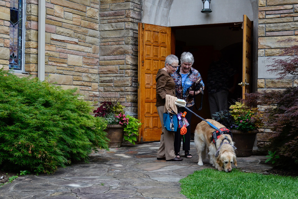 Peggy Gibson (left) guides her diabetic alert dog Rocky outside as she talks with a friend following a church service at Bethany United Methodist Church in West Jefferson, N.C., on July 7, 2019. The congregation helped Gibson raise the money to purchase Rocky.