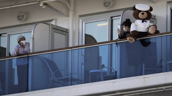 A woman with a teddy bear waves to another passenger as they undergo quarantine on the Diamond Princess cruise ship in Yokohama, near Tokyo. Many passengers are using chat groups and social media to share information with each other.