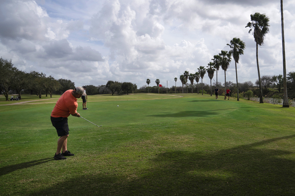 Memo Ibarra makes a chip shot at River Bend Resort & Golf Club in Brownsville, Texas. The 18-hole golf course would have 15 of them on the south side of Trump's proposed border wall.