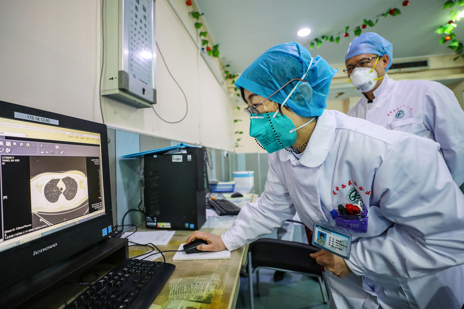 A doctor wearing a face mask looks at a CT image of a lung of a patient at a hospital in Wuhan, China. (AFP via Getty Images)