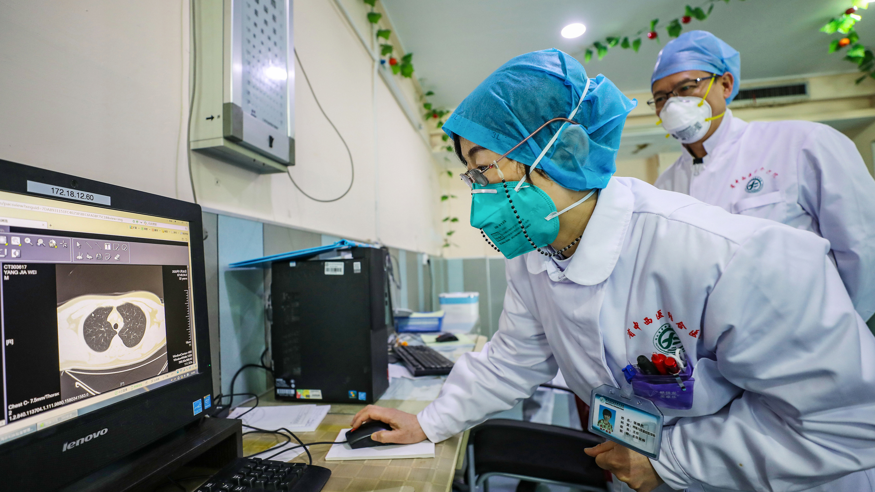 A doctor wearing a face mask looks at a CT image of a lung of a patient at a hospital in Wuhan, China.