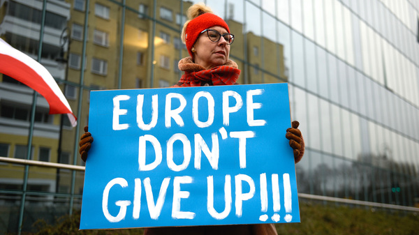 A pro-democracy protestor holds a placard ahead of a meeting between the Vice President of the European Commission for Values and Transparency, Vera Jourova, and the First President of Poland