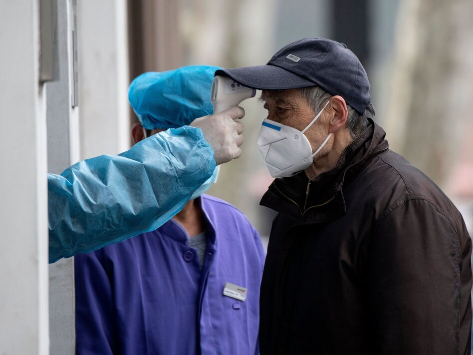 A man wearing a face mask has his temperature checked before entering a community hospital in Shanghai on Thursday. China's official death toll and infection numbers from the deadly COVID-19 coronavirus spiked dramatically on Thursday after authorities changed their counting methods. (Noel Celis/AFP via Getty Images)