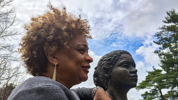 JerriAnne Boggis, executive director of the Black Heritage Trail of New Hampshire, poses with a monument that was erected in Harriet E. Wilson