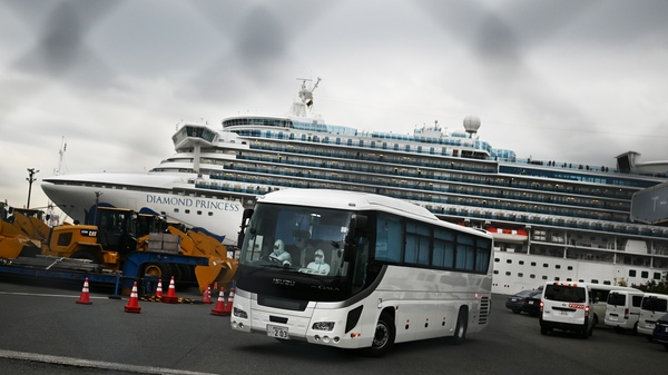 A bus departs from the dock where the Diamond Princess cruise ship sits under quarantine with its thousands of passengers and crew. Japanese authorities said Friday that some older passengers who tested negative for the coronavirus were allowed to disembark.