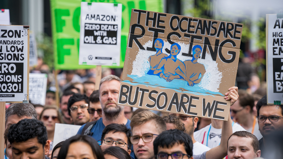 """A protester holds a sign reading """"The Oceans Are Rising But So Are We"""" at an Amazon employee walkout in Seattle, as part of the Global Climate Strike on Sept. 20, 2019. At some companies, employees are putting increasing pressure on their bosses to act on climate change. (Chloe Collyer/Bloomberg via Getty Images)"""