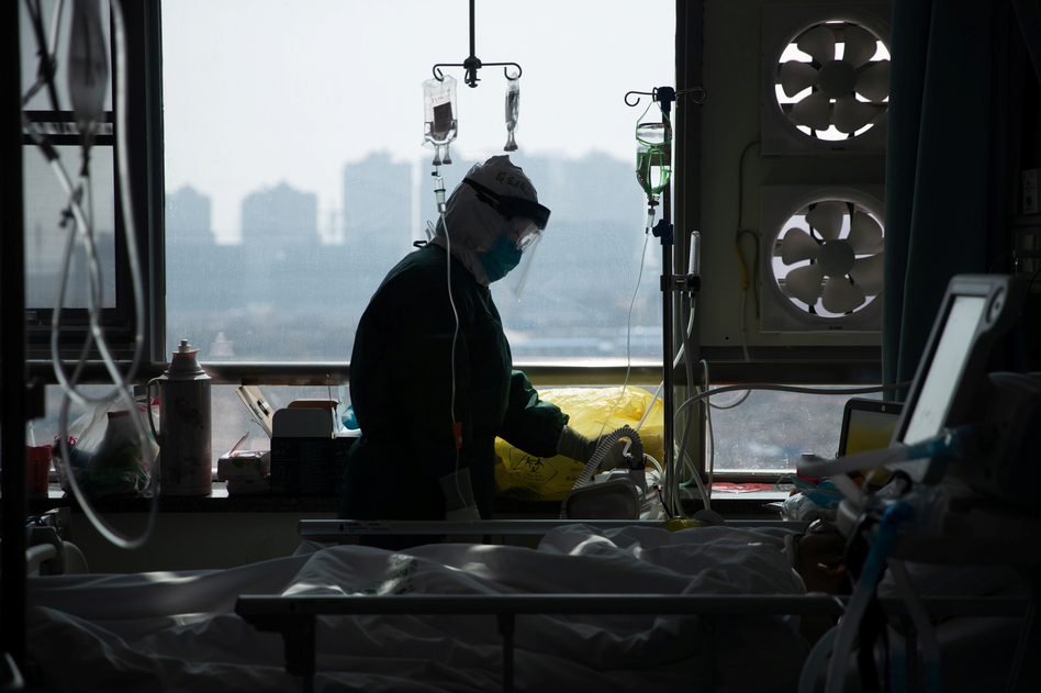 A medical worker in a protective suit tends to a patient in a hospital in Wuhan, China. (China Daily CDIC/Reuters)