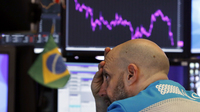 Specialist Meric Greenbaum works at his post on the floor of the New York Stock Exchange on Tuesday. Stocks slumped and bond prices soared for the second day in a row as fears spread that the widening coronavirus outbreak will put the brakes on the global economy.
