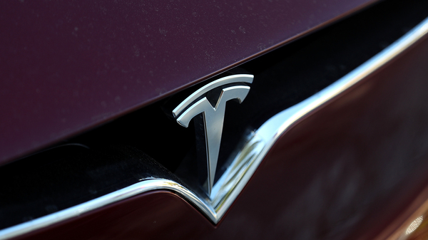 The Tesla logo is displayed on the front of a Tesla Model X in Los Angeles in 2017.