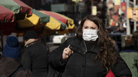 A woman wears a mask in New York out of concern for the newly emerged coronavirus. However, experts say that the commonly worn surgical masks aren't very effective protection.