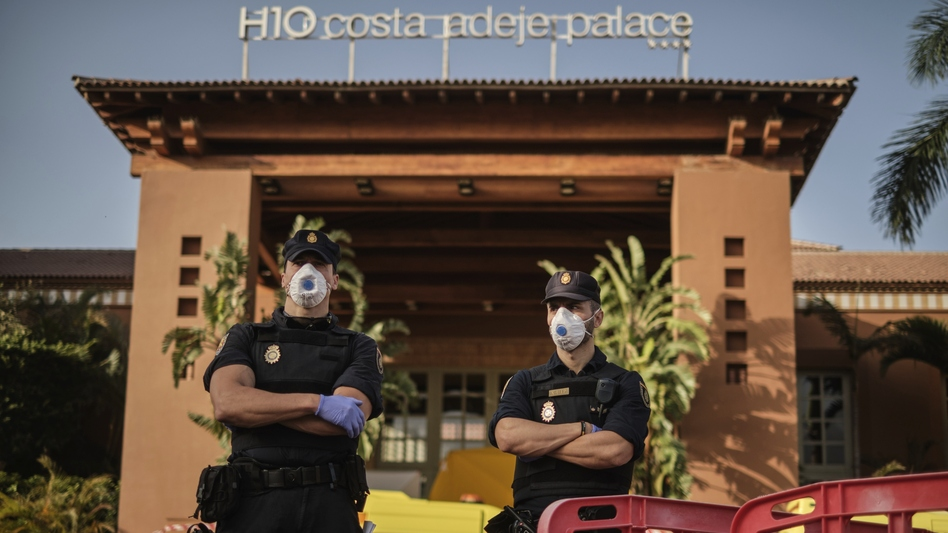 Police officers wear face masks Wednesday in front of a hotel on Tenerife, the largest of Spain's Canary Islands. Spanish officials say a hotel on the island has been placed under quarantine after an Italian doctor staying there tested positive for the new coronavirus. (AP)