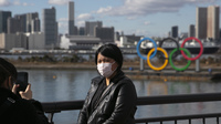 A tourist wearing a mask poses for a photo with the Olympic rings in the background, at Tokyo's Odaiba district, in a photo taken last month.