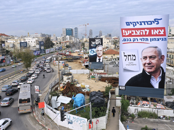 """Billboards show Benjamin Netanyahu (right) and rival candidate Benny Gantz in Bnei Brak, Israel, on Feb. 23. The sign in the foreground, for Netanyahu's Likud party, reads """"Likud members, go out to vote, victory depends only on you."""""""