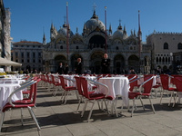 Waiters stand by an empty restaurant in Venice's St. Mark's Square, which would normally be full of tourists, as a coronavirus outbreak grows in Italy.