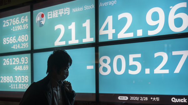 A pedestrian walks past a board displaying the closing figure of the Nikkei Stock Average in Tokyo on Friday. All of the major indexes are now in what the markets call a correction, and stocks also were down in Asia and Europe.