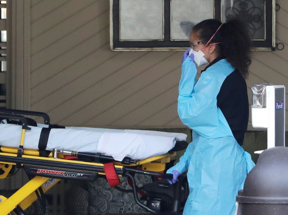 An ambulance worker adjusts her protective mask Saturday as she wheels a stretcher into a nursing facility in Kirkland, Wash., where more than 50 people were found to be sick and are being tested for COVID-19 virus. (Elaine Thompson/AP)