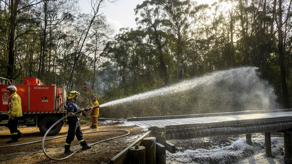 A firefighter coats a bridge with foam as a bushfire burns near Moruya, New South Wales, Australia, on Jan. 25. Wildfires destroyed more than 3,000 homes and razed more nearly 11 million hectares since the summer fires began.