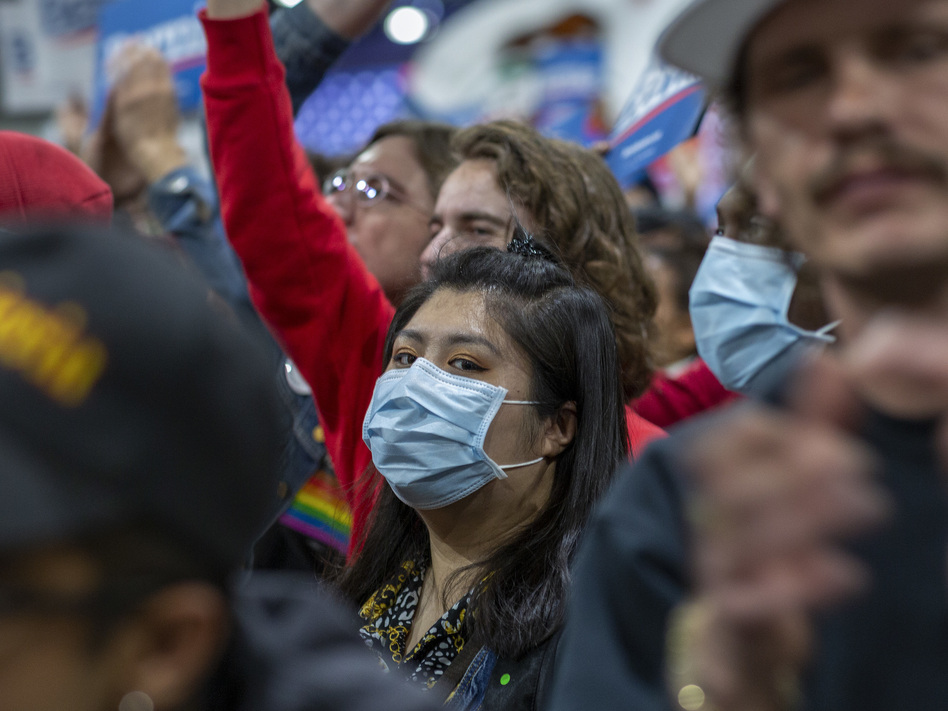 A woman in California wears a medical mask during a political campaign rally. (David McNew/Getty Images)
