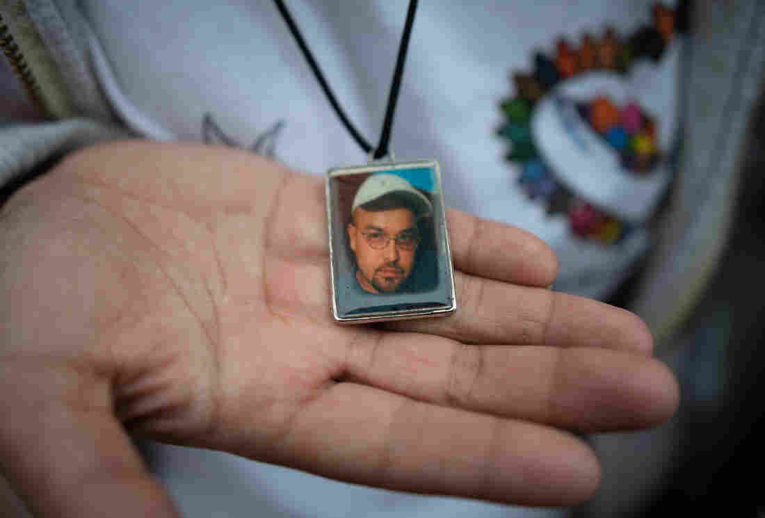 A woman shows a pendant with a portrait of Gustavo Trujillo, who disappeared in 2010 in Poza Rica, Veracruz, Mexico.