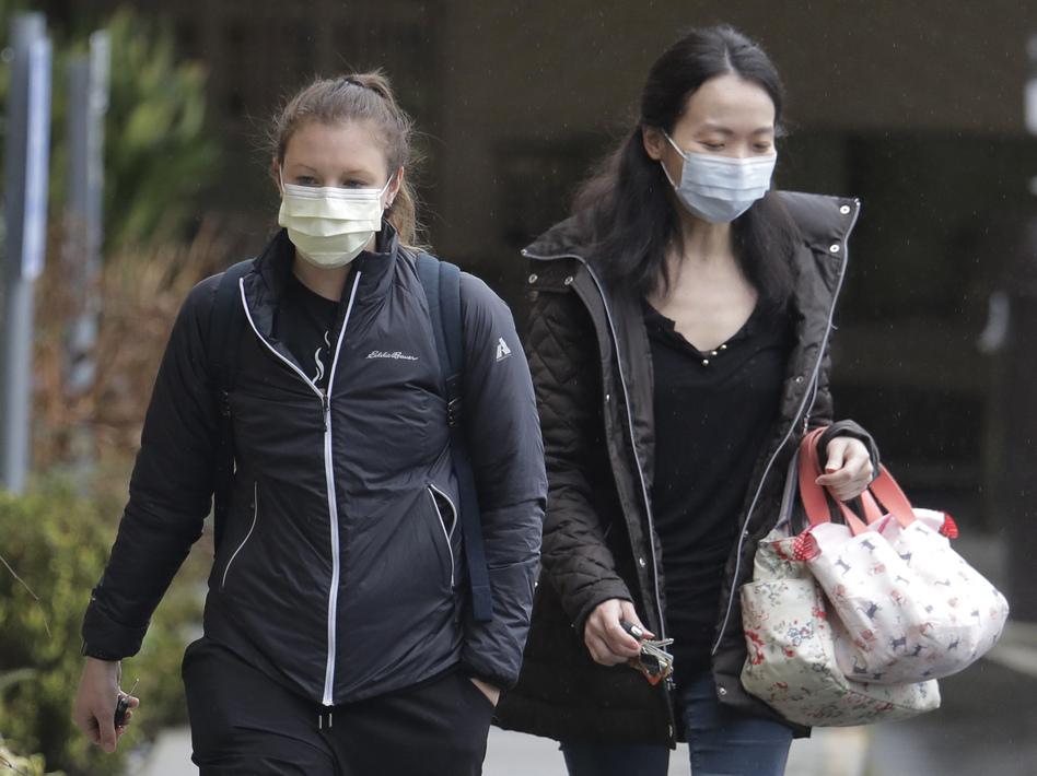 Two women wearing masks walk away from the Life Care Center in Kirkland, Wash., near Seattle. An outbreak of the coronavirus is cited as the cause for the deaths of at least two residents at the center. (Ted S. Warren/AP)