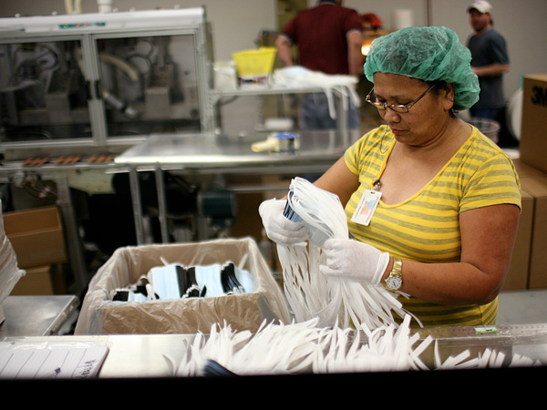A Prestige Ameritech employee inspects disposable surgical masks May 3, 2009, at the company's Texas factory. The company is one of the last domestic manufacturers of medical face masks.