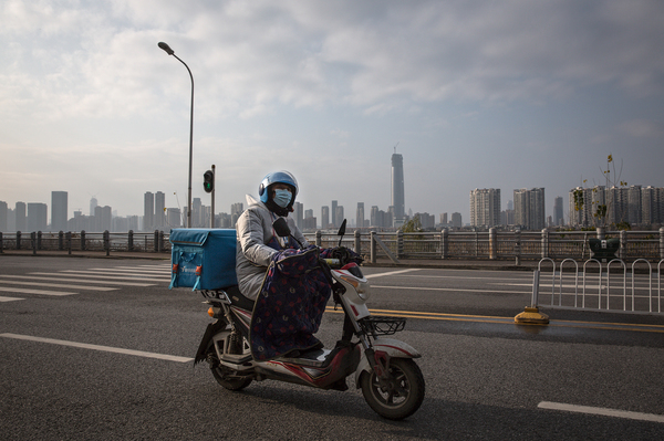 A delivery worker on a motorcycle on an empty street in Wuhan. Despite the city's lockdown measures to prevent the spread of disease, a handful of delivery companies are still in operation. Their workers provide supplies and necessities to residents cooped up in their homes.