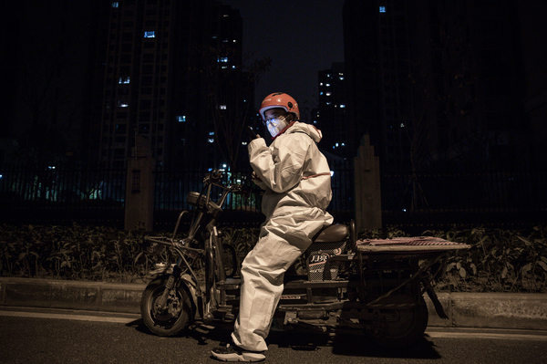 A courier in protective gear on his motorcycle.
