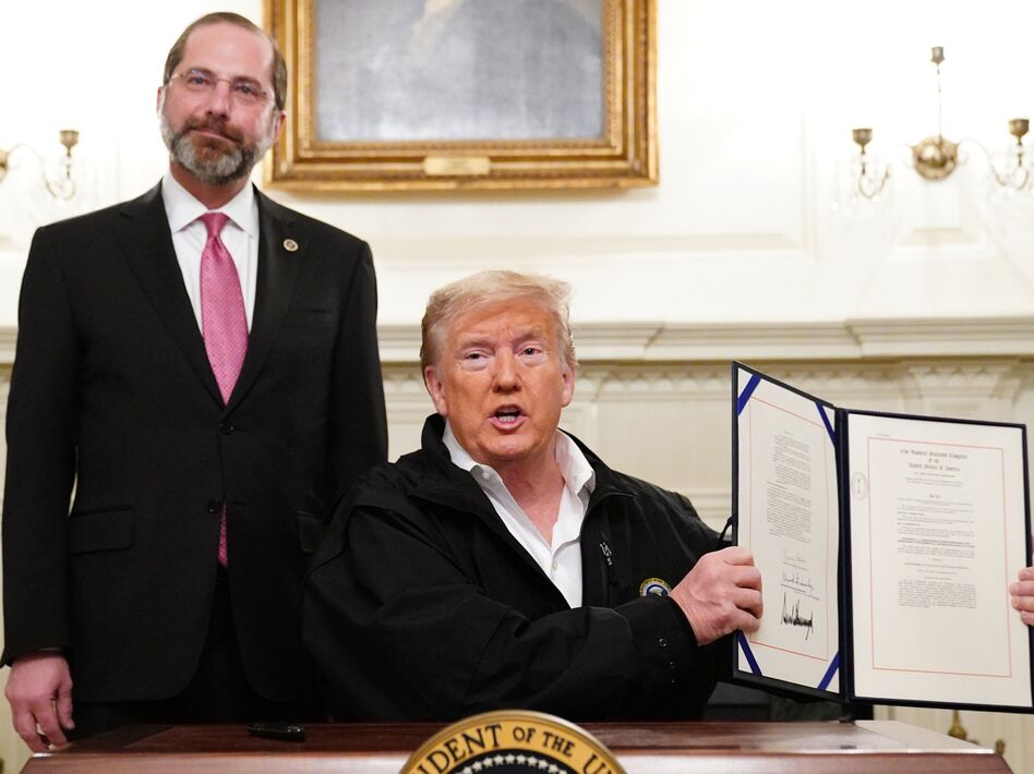 President Trump holds up the $8 billion coronavirus emergency funding bill after signing it at the White House as Health Secretary Alex Azar looks on. (Mandel Ngan/AFP via Getty Images)