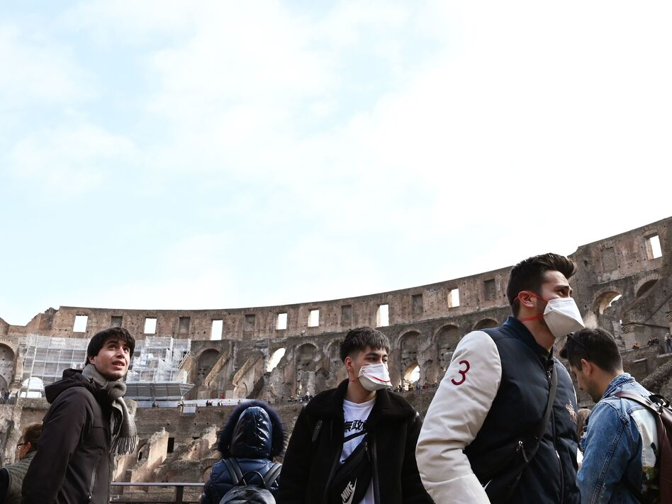 Tourists wearing respiratory masks visit the Coliseum in Rome on Friday. Italy's coronavirus cases have continued to rise, making it one of the hardest-hit countries. (Tiziana Fabi/AFP via Getty Images)