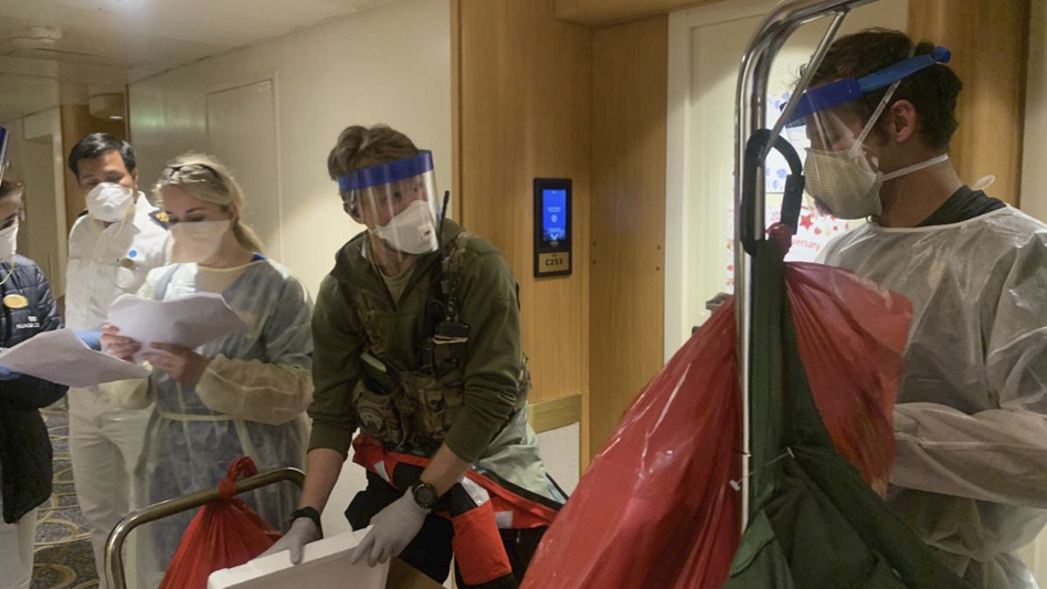 A group of medical personnel with the CDC and the California National Guard 129th Rescue Wing don protective equipment after delivering virus testing kits to the Grand Princess cruise ship off the coast of California. (Chief Master Sgt. Seth Zweben/California National Guard via AP)