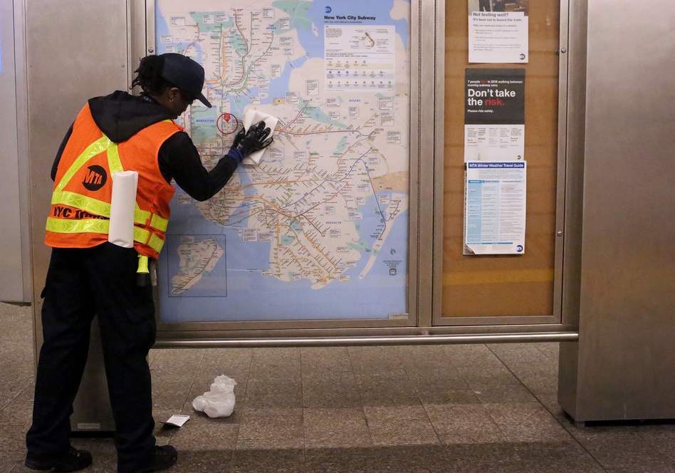A metro transit authority cleaning staff member disinfects the 86th St. Q train station in New York City. (Yana Paskova/Getty Images)