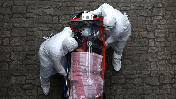 Medical staff in protective gear move a patient with COVID-19 from an ambulance to a hospital in Seoul.