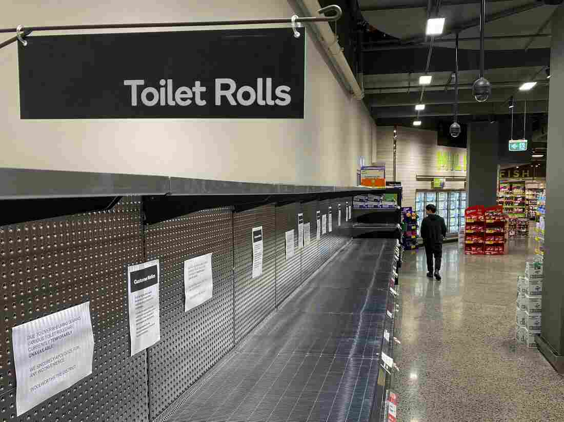 A shopper passes empty shelves usually stocked with toilet paper in a supermarket