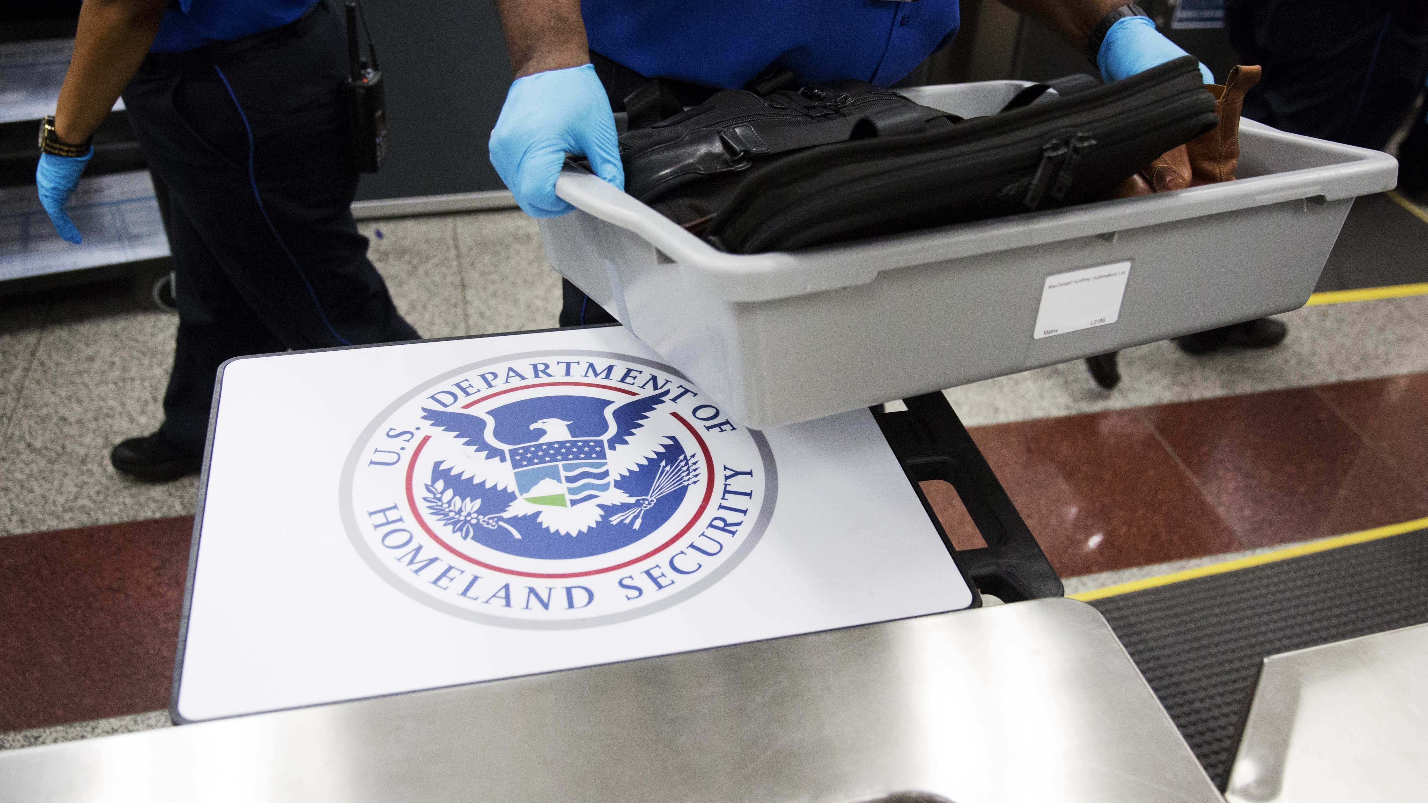 A U.S. Department of Homeland Security seal is seen as a TSA official moves a bin for additional screening at Hartsfield-Jackson Atlanta International Airport.