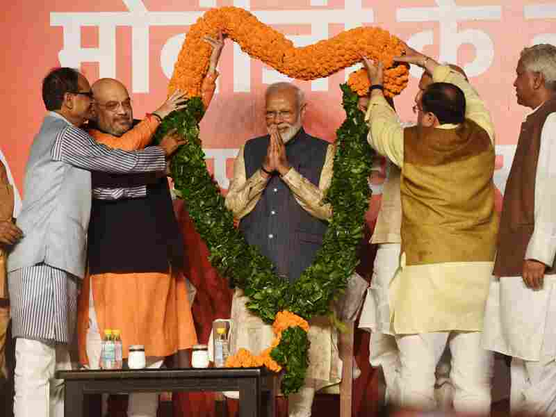 """Indian Prime Minister Narendra Modi as he is draped by the Bharatiya Janta Party (BJP) president Amit Shah and other senior leaders as they celebrate Modi's victory on May 23, 2019. Prime Minister Narendra Modi vowed an """"inclusive"""" future for all Indians after a landslide election."""