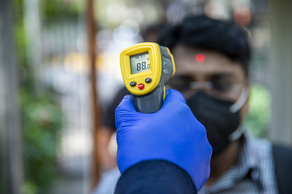 An office worker is screened with an infrared thermometer as he enters a building in New Delhi, India.