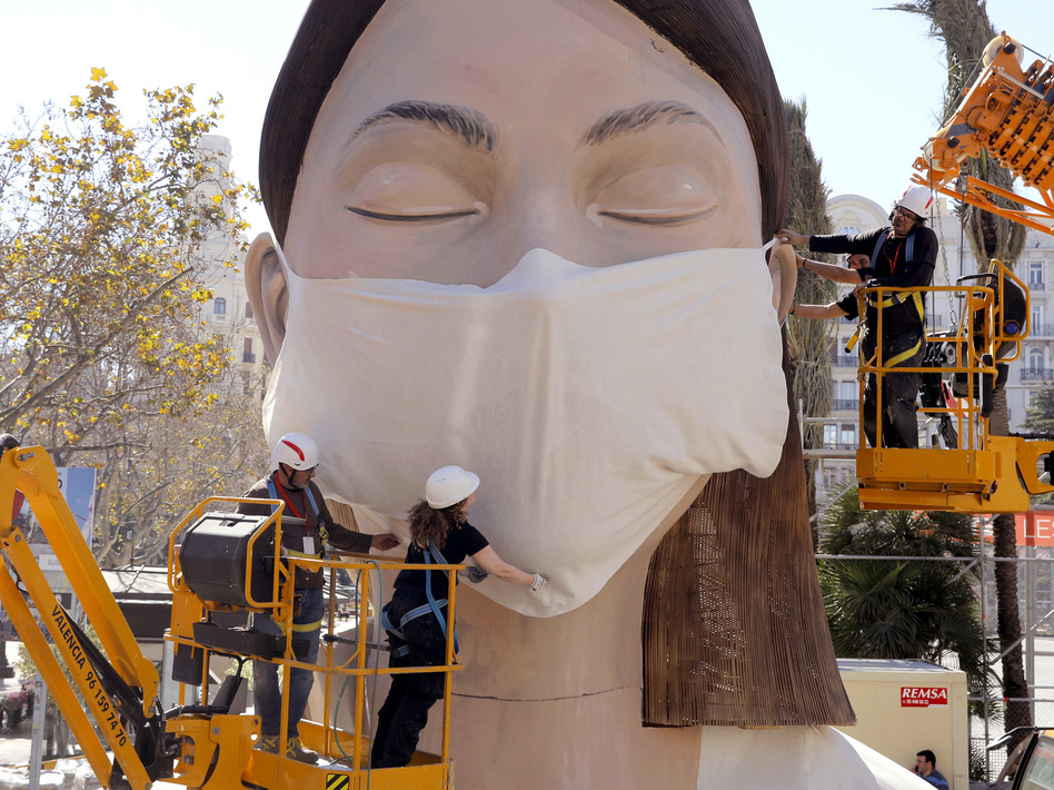 The World Health Organization called the COVID-19 viral disease a pandemic Wednesday. Here, workers in Spain place a medical mask on a figure that was to be part of the Fallas festival in Valencia. The festival has been canceled over the coronavirus outbreak. (Alberto Saiz/AP)