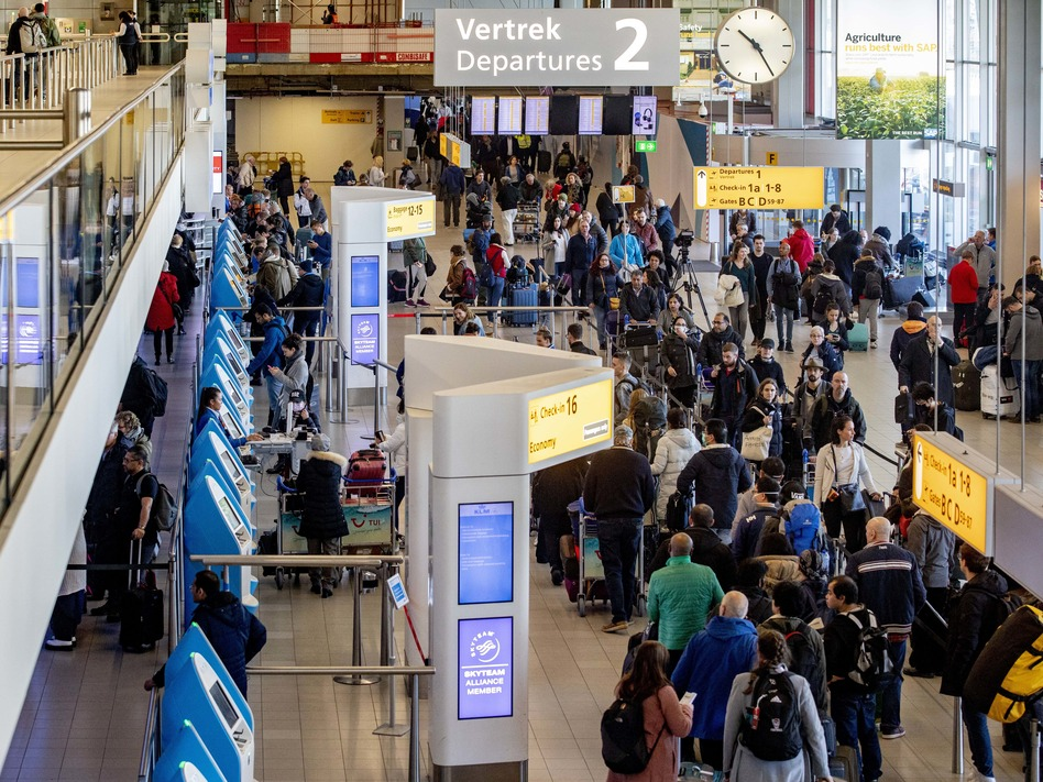Passengers hoping to change their flights to the U.S. wait in long lines at Amsterdam Airport Schiphol in the Netherlands after President Trump announced new restrictions on travel from Europe. (Niels Wenstedt/Barcroft Media via Getty Images)