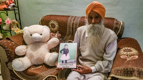 Gurmeet Singh holds a photo of his granddaughter, Gurupreet Kaur, who died of heatstroke in Arizona in June 2019. The 6-year-old and her mother had just crossed into the U.S. from Mexico.