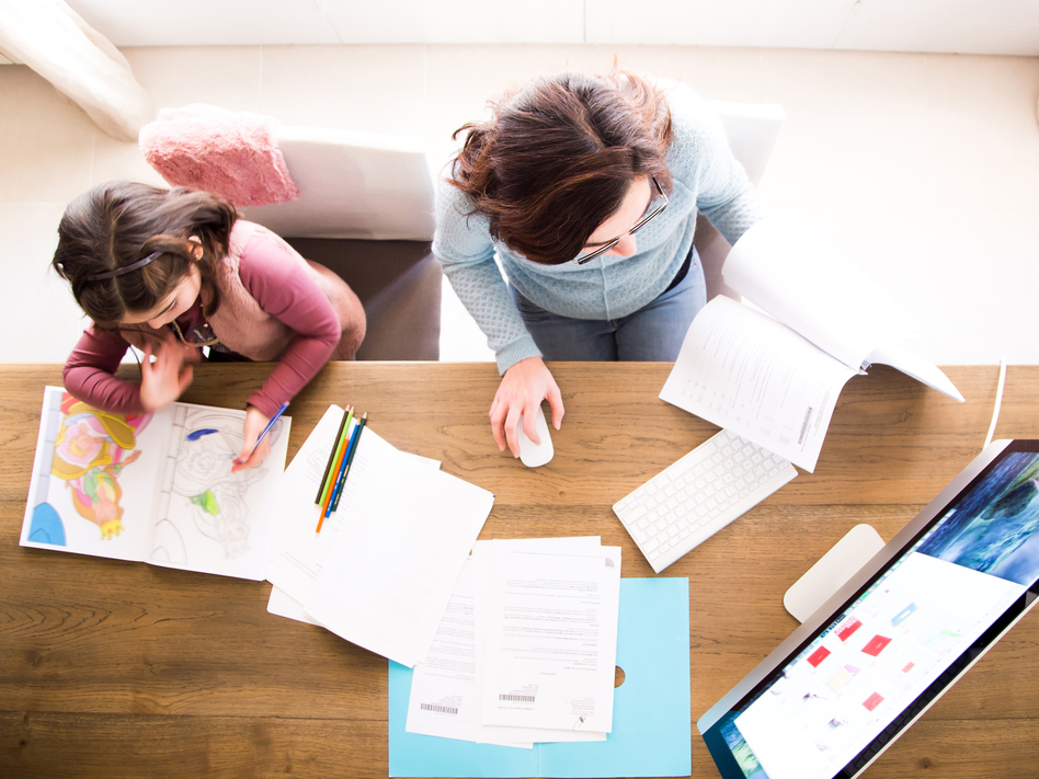 Many parents suddenly have the task of making sure their kids learn while adjusting to a new life of managing working from home. (Artur Debat/Getty Images)