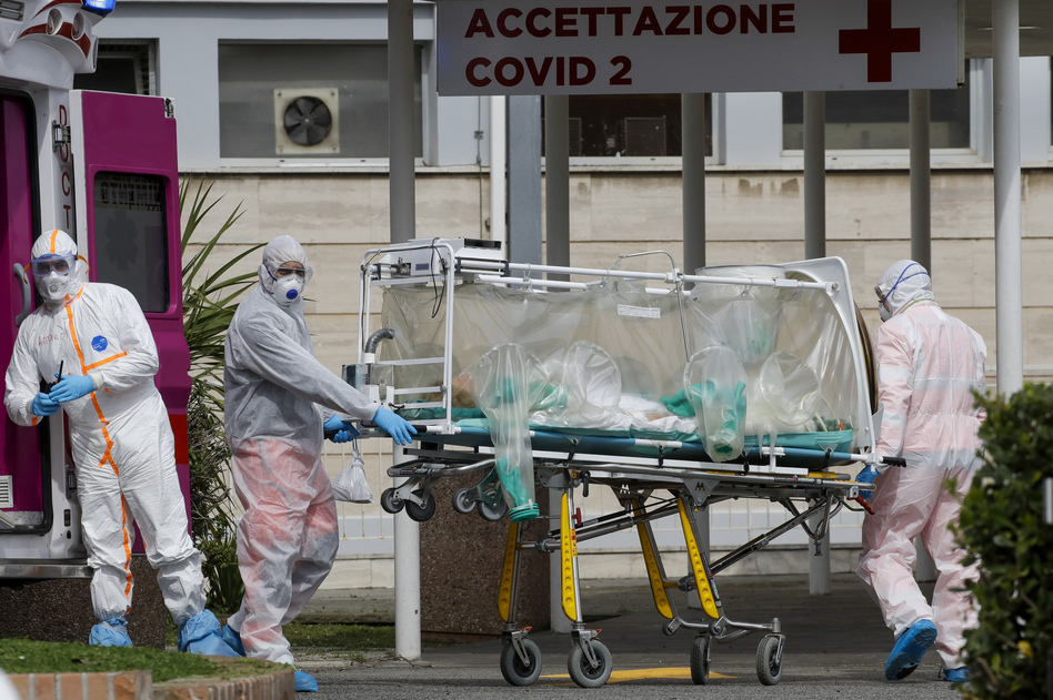 A patient in a biocontainment unit is carried on a stretcher from an ambulance at the Columbus Covid 2 Hospital in Rome, on Tuesday. Italy's health system is straining to keep up with quickly rising coronavirus cases. (Alessandra Tarantino/AP)