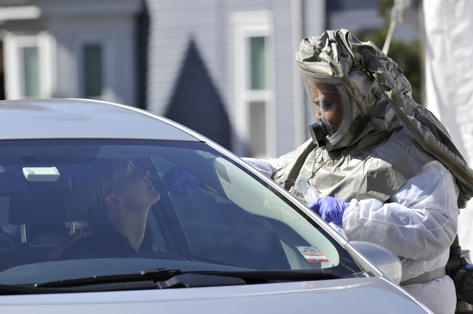 A medical professional takes samples from person at a drive-through coronavirus testing lab set up at Somerville Hospital in Somerville, Mass., on Wednesday. (Joseph Prezioso/AFP via Getty Images)