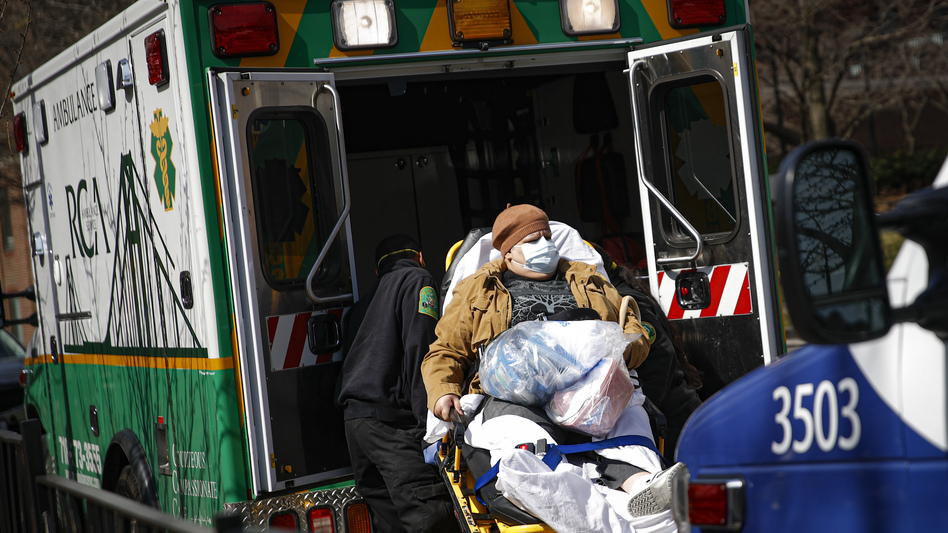 Medical workers load a patient wearing a protective mask into the back of an ambulance Wednesday outside a hospital in Brooklyn. New York has seen a spike in coronavirus cases, and officials are preparing for an influx at medical centers throughout the state. (John Minchillo/AP)