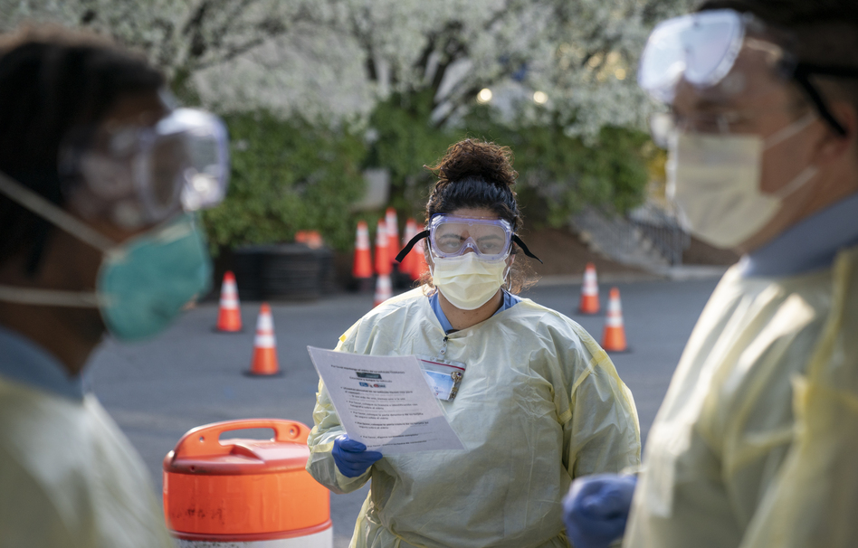 Jessica Mendoza (center), a Virginia Hospital Center outpatient lab specialist, and James Meenan (right), the director of the Virginia Hospital Center outpatient lab, make final preparations before opening a drive-through coronavirus testing site on Wednesday in Arlington, Va. President Trump signed a bill Wednesday that includes funding for testing. (Drew Angerer/Getty Images)