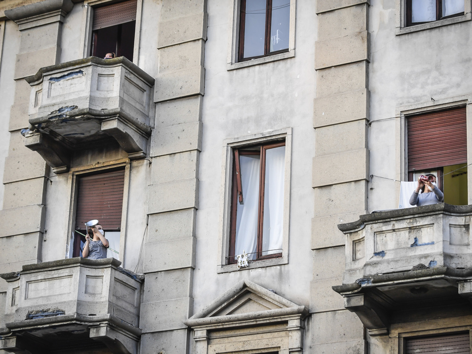 People lean out of their homes' balconies to play and sing during a flash mob in Milan, Italy, Friday, March 13, 2020. Italians have not been able to leave their homes since March 9, when the government locked the country down to combat the spread of coronavirus. (Claudio Furlan/AP)