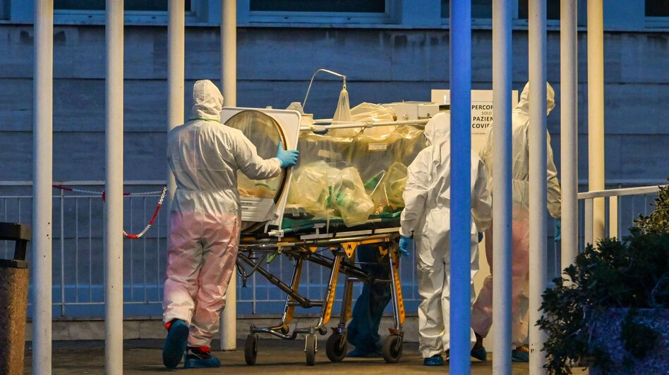 Medical workers transport a patient into a newly built temporary hospital on March 16 in Rome. Doctors in Italy are making difficult decisions about who should receive care. (Andreas Solaro/AFP via Getty Images)