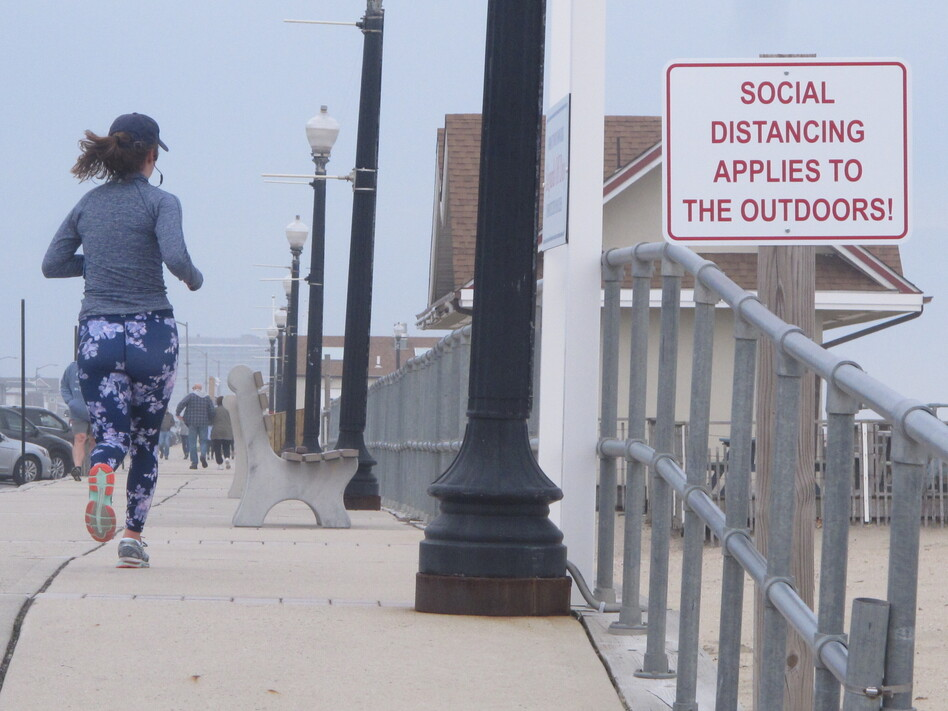 A sign on the Bradley Beach, N.J., oceanfront urges people to practice social distancing even in the outdoors during the coronavirus outbreak. On Saturday, New Jersey Gov. Phil Murphy signed an executive order directing all residents to stay at home. (Wayne Parry/AP)