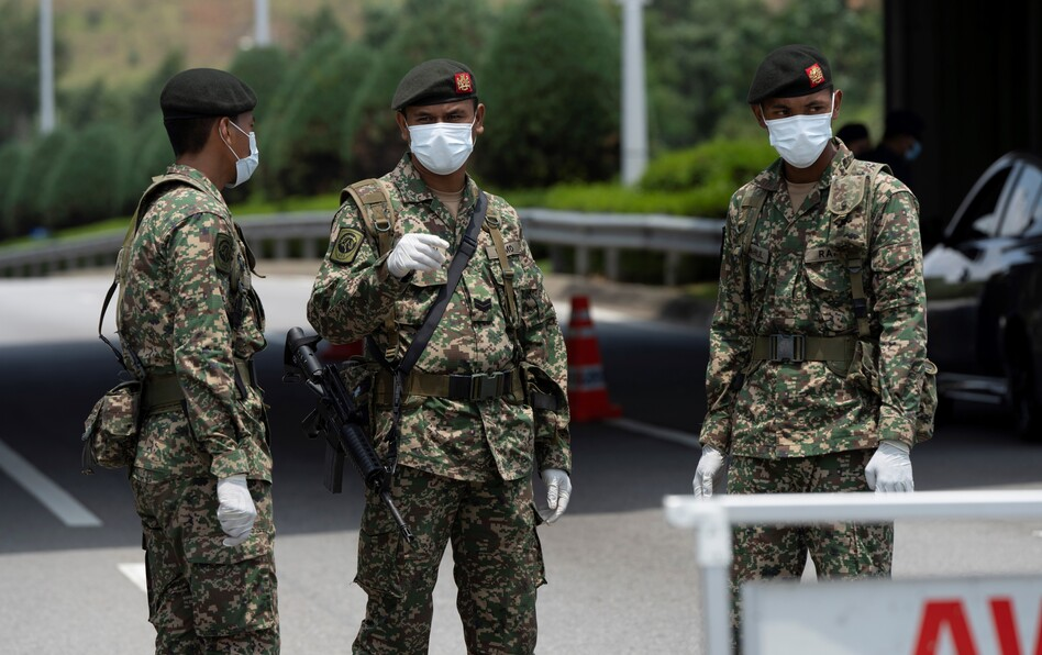 Soldiers in face masks maintain a checkpoint in Putrajaya, Malaysia, on Sunday. The Malaysian government issued a movement order to the public until March 31 to stop the spread of the new coronavirus. (Vincent Thian/AP)