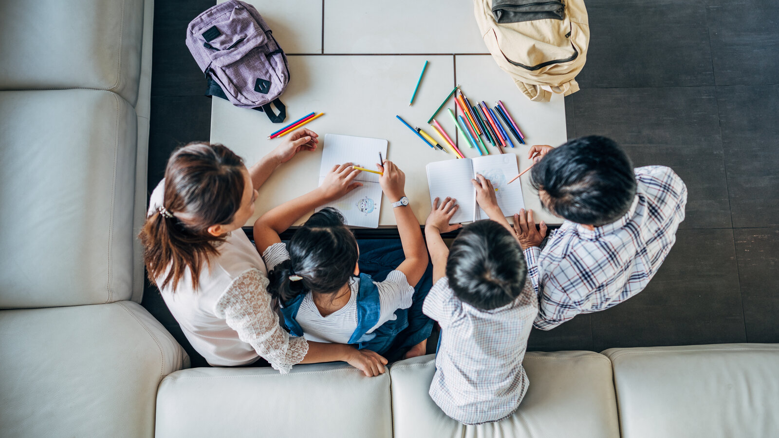 Group of people, parents doing homework with two children together at home.